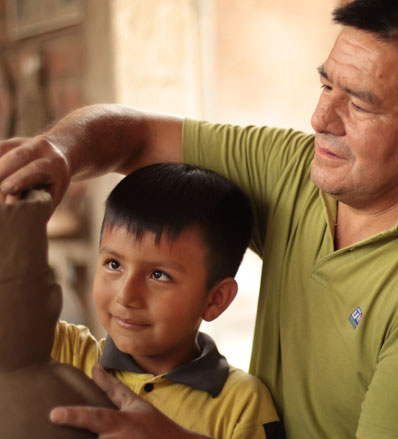 Walter Jose Acosta teaches his son how to sculpt